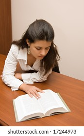 Young woman reading a book at the desk.