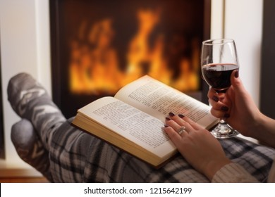 Young woman reading book and drinking red wine in front of the fireplace and warming feet in wool socks. Girl legs is covered with blanket. Winter long cold night concept. Close up, selective focus