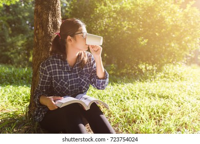 young woman reading book and drinking coffee from cup in park