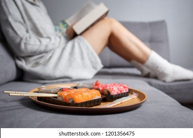 Young woman reading book and eating sushi on the sofa at home