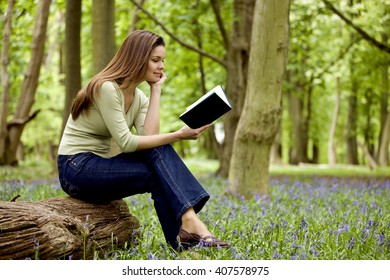A young woman reading a book in a field of bluebells
