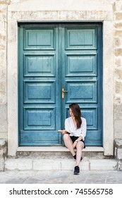 Young woman reading a book. Green door background