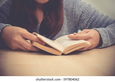 Young woman reading a book, Hand focus, Vintage style.