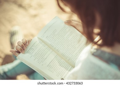 A young woman reading a book. Book in woman hands.
