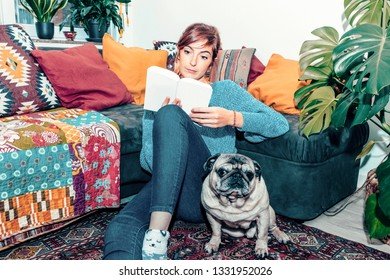 young woman reading a book in his home with her pet - chill out concept - singles life concept