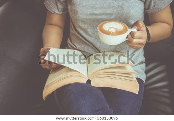 本を読み、コーヒーを飲む若い女性