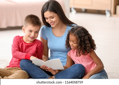Young woman reading book to little kids indoors. Child adoption