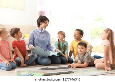 Young woman reading book to little children indoors. Learning by playing
