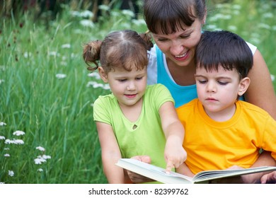 Young woman reading book little girl and cute boy in a meadow