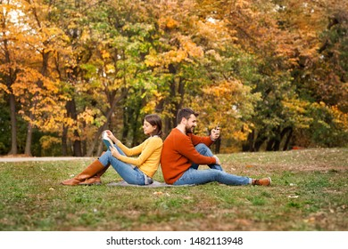Young woman reading book and man using mobile phone while relaxing in autumn park. Diversity connects us