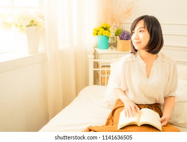 Young woman reading a book in morning