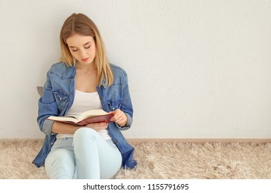 Young woman reading book on floor near light wall