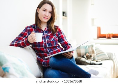 Young woman reading book on sofa relaxing at home