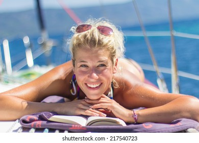 Young woman reading a book on a sailing boat