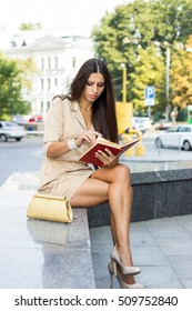 Young woman reading book on the street
