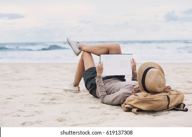 Young woman reading a book on the beach. Relaxation resting vacations concept
