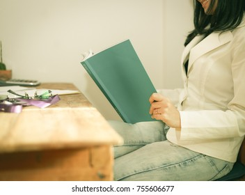 young woman  reading a book on wood desk at home