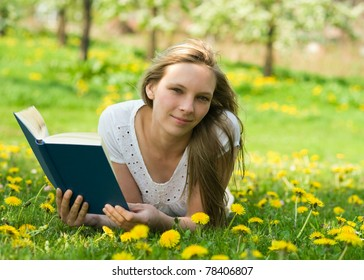 Young woman reading the book on green meadow