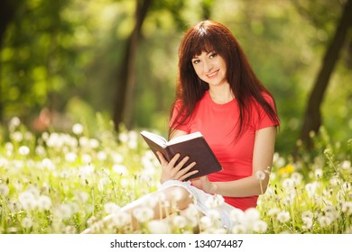 Young woman reading a book in the park with flowers
