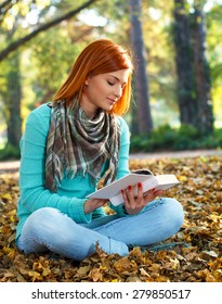 Young woman reading a book in park.