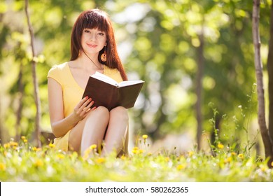Young woman reading a book in the park with flowers. Beauty nature scene with colorful background, trees and flowers at summer season. Outdoor lifestyle. Happy smiling woman relax on green grass