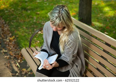 Young woman reading book with pencil in hand on a bench at an autumn park.