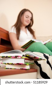 Young woman is reading book. Primary focus on stack of books