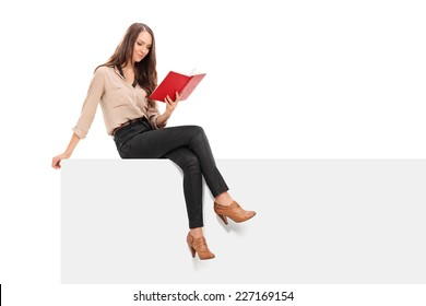 Young woman reading a book seated on a panel isolated on white background