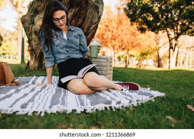 Young woman reading a book sitting on a blanket at the park. Relaxed woman reading novel with juice in hand.
