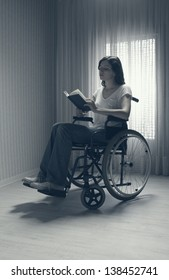 Young woman reading a book sitting on the wheelchair against a window