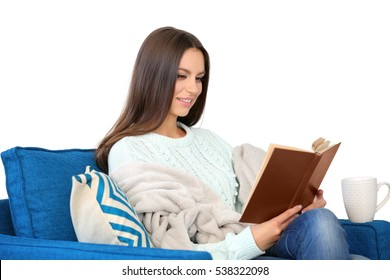 Young woman reading book sitting at comfortable armchair, interior background