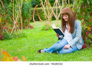 Young woman reading a book sitting on the grass in a park