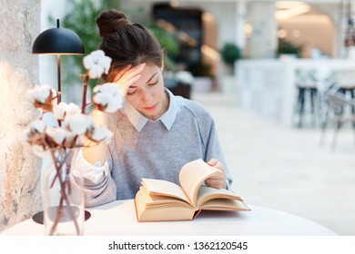 Young woman is reading book under warm table lamp light. Student is studying in modern library. Girl is tired.