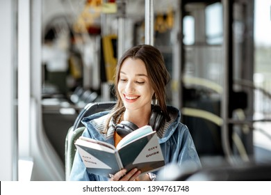 Young woman reading book while moving in the modern tram, happy passenger at the public transport
