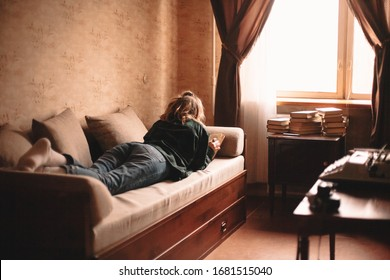 Joven leyendo un libro mientras está acostado en el sofá de casa