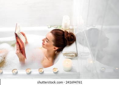 Young woman reading book while lying in the bath with foam and candles