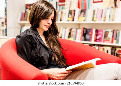Young woman reading books in a bookstore