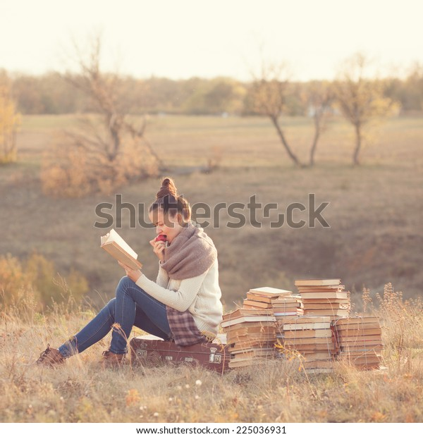 Young woman reading a books and eating apple outdoors