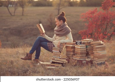 Young woman reading a books outdoors