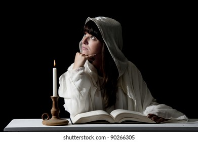young woman reading with candle light on dark background