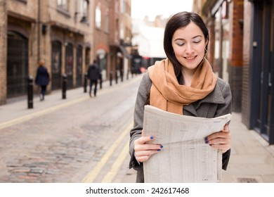 young woman reading her paper in the street