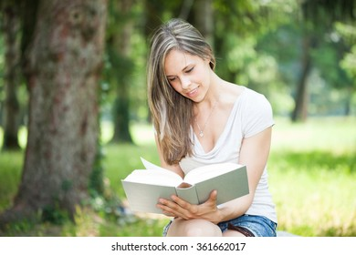 Young woman reading a large book in a park