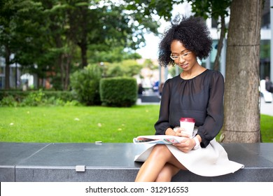 young woman reading a magazine with a coffee