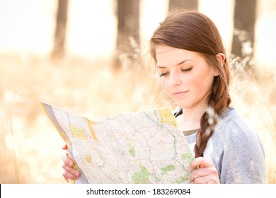 Young Woman Reading Map - This is a photo of a cute young woman sitting in tall grass in the woods reading a map.