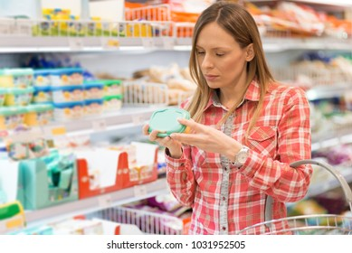 Young woman reading nutrition label on diary food in local supermarket.
