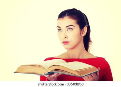 Young woman reading an old book.