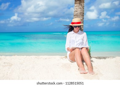 Young woman reading on tropical white beach sitting in the shade of a palm tree