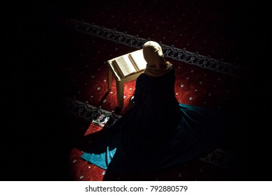 Young woman reading Quran in the mosque