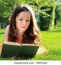 Young woman reading in summer park