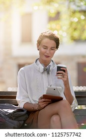 young woman reading tablet and enjoying coffee